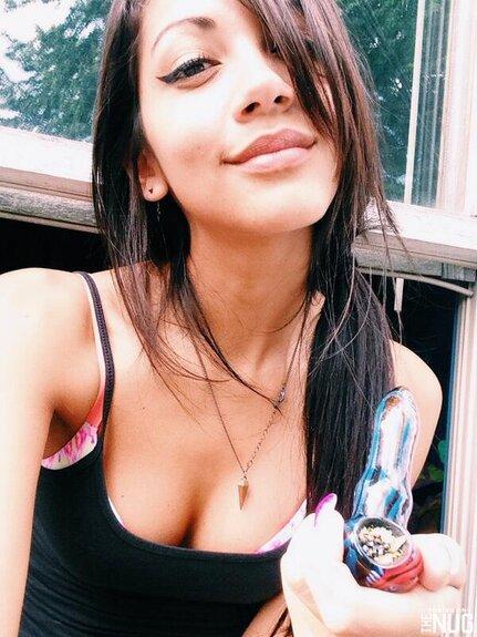 beautiful brunette girl smoking weed pipe