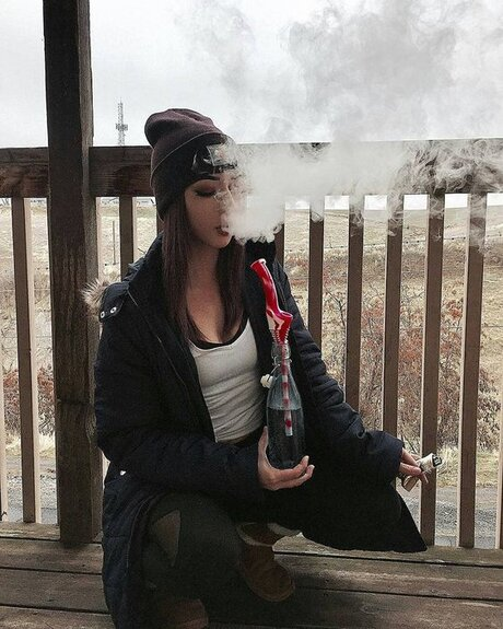 girl wearing beanie smoking bong outside